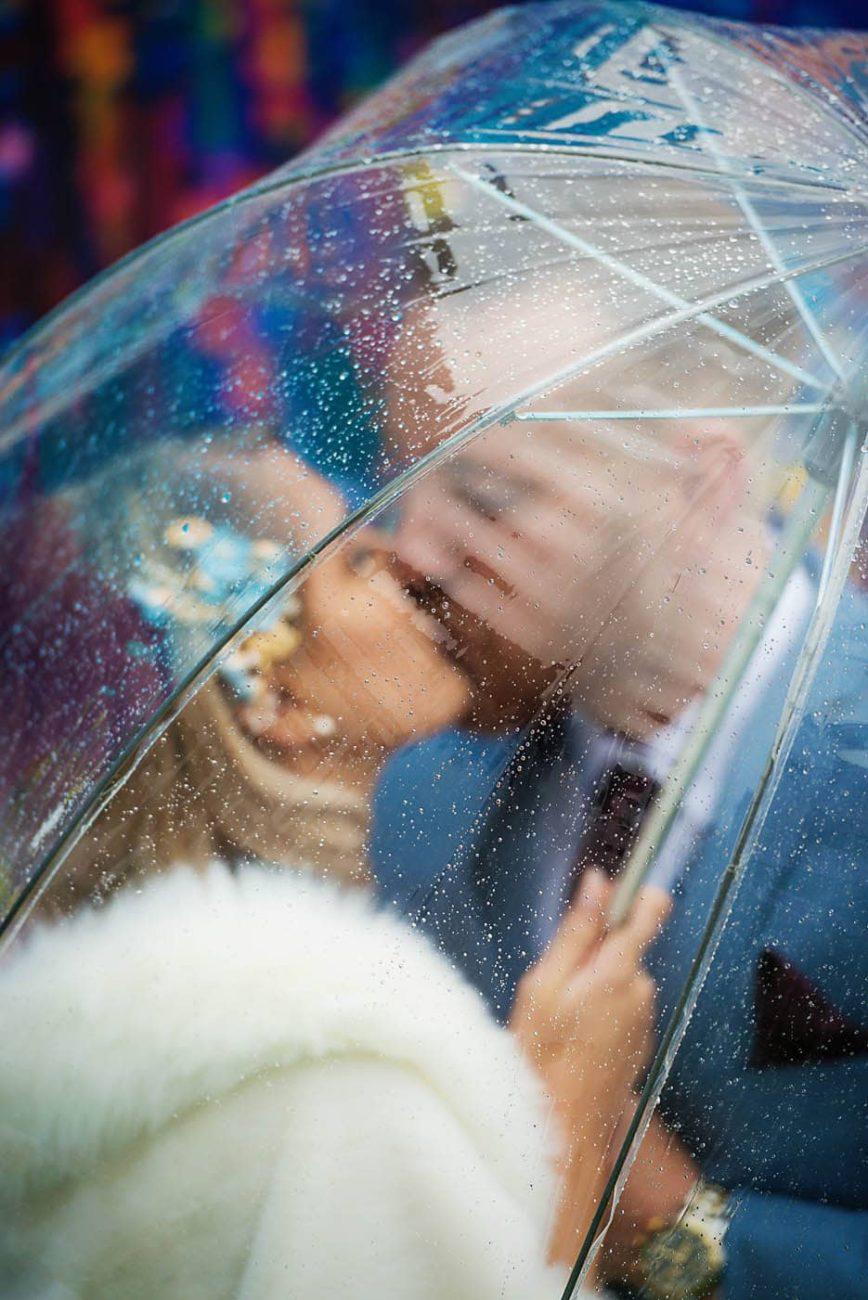 Bride Groom kissing on rainy day behind umbrella