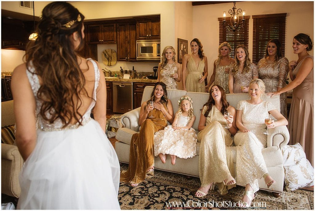Brides maids looking at the  bride for the first time in her wedding dress