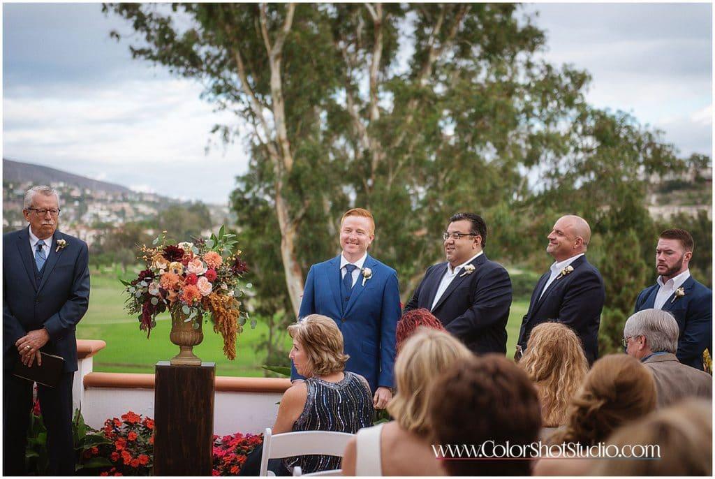 Groom looking at bride walking down the isle